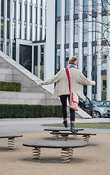 Young woman jumping on trampoline in playground, Munich, Bavaria, Germany