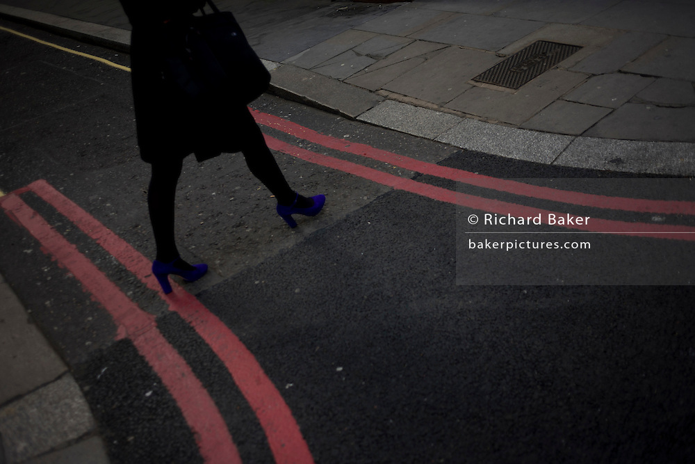 Legs of a woman wearing bright purple shoes crosses a Red Route lines in a London street.