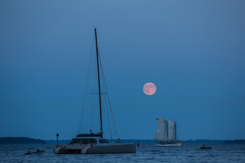 Camden, ME - 10 August 2014. The Supermoon over Camden, catamaran Zenyatta at anchor.