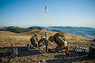 Gunner PFC Darnell, left, and his assistant gunner PFC Beat take cover while firing a 60mm mortar during live-fire exercises for the 2nd Battalion, 5th Marine Regiment at Camp Pendleton.