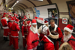 © Licensed to London News Pictures./14/2013. London, UK. Participants dressed in Father Christmas costumes gather for the annual Santacon celebration at Camdem Town Station.Photo credit : Peter Kollanyi/LNP
