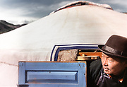 A nomadic Mongolian herder gets out of his yurt, wearing a bowler hat.