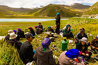 Tibetan people with 45 mile long Yamdrok Tso Lake (14,570 feet) in the background. It is the largest lake and one of the three sacred lakes in Tibet (Xizang), China.