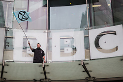 London, UK. 11 October, 2019. A climate activist from Extinction Rebellion stands with a flag on the glass parapet above the main entrance to the BBC's New Broadcasting House on the fifth day of International Rebellion protests. They were demanding that the broadcaster 'tell the truth' regarding the climate emergency.