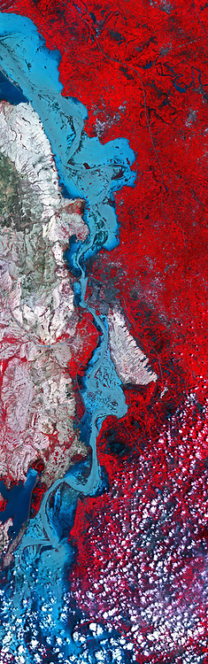 On Sept. 3, 2010, when the Advanced Space borne Thermal Emission and Reflection Radiometer (ASTER) instrument on NASA's Terra spacecraft captured this image strip over the Indus River, Pakistan, severe flooding was still causing a major humanitarian crisis in the country. The city of Hyderabad is near the middle of the image. In this false-colour image, vegetation appears red, water is medium to dark blue and non-vegetated hills are light tan. The ASTER image is located at 25.2 degrees north latitude, 68.4 degrees east longitude. The image covers an area of 60 by 169 kilometres (37 by 118 miles).With its 14 spectral bands from the visible to the thermal infrared wavelength region and its high spatial resolution of 15 to 90 meters (about 50 to 300 feet), ASTER images Earth to map and monitor the changing surface of our planet. ASTER is one of five Earth-observing instruments launched Dec. 18, 1999, on Terra. The instrument was built by Japan's Ministry of Economy, Trade and Industry. A joint U.S./Japan science team is responsible for validation and calibration of the instrument and data products. The broad spectral coverage and high spectral resolution of ASTER provides scientists in numerous disciplines with critical information for surface mapping and monitoring of dynamic conditions and temporal change. Example applications are: monitoring glacial advances and retreats; monitoring potentially active volcanoes; identifying crop stress; determining cloud morphology and physical properties; wetlands evaluation; thermal pollution monitoring; coral reef degradation; surface temperature mapping of soils and geology; and measuring surface heat balance.