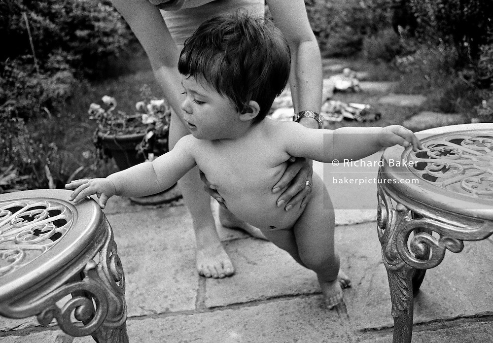 """Garden ballet."" With hands outstretched, a ten month-old infant supports her weight on some garden chairs as she learns to stand on her own two feet. Without the strength in her legs, she loses her balance and her mother stands behind holding her daughter by the waist preventing her from falling over. It is a warm summer afternoon with both mother and child barefoot on the back garden patio and we see the experience of an adult encouraging a developing human being with the confidence to stand erect with back straight. This is from a documentary series of pictures about the first year of the photographer's first child Ella. Accompanied by personal reflections and references from various nursery rhymes, this work describes his wife Lynda's journey from expectant to actual motherhood and for Ella - from new-born to one year-old."
