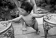 """""""Garden ballet."""" With hands outstretched, a ten month-old infant supports her weight on some garden chairs as she learns to stand on her own two feet. Without the strength in her legs, she loses her balance and her mother stands behind holding her daughter by the waist preventing her from falling over. It is a warm summer afternoon with both mother and child barefoot on the back garden patio and we see the experience of an adult encouraging a developing human being with the confidence to stand erect with back straight. This is from a documentary series of pictures about the first year of the photographer's first child Ella. Accompanied by personal reflections and references from various nursery rhymes, this work describes his wife Lynda's journey from expectant to actual motherhood and for Ella - from new-born to one year-old."""