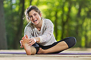 Stock photo of a girl laughing while stretching a practicing yoga at a park.