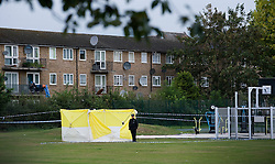 © Licensed to London News Pictures. 18/08/2011. A policeman stands over a forensics tent in Ponders End Recreation Ground in Enfield, London today (18/08/2011) where a 14 Year-old boy was found stabbed to death yesterday afternoon. Photo credit: Ben Cawthra/LNP