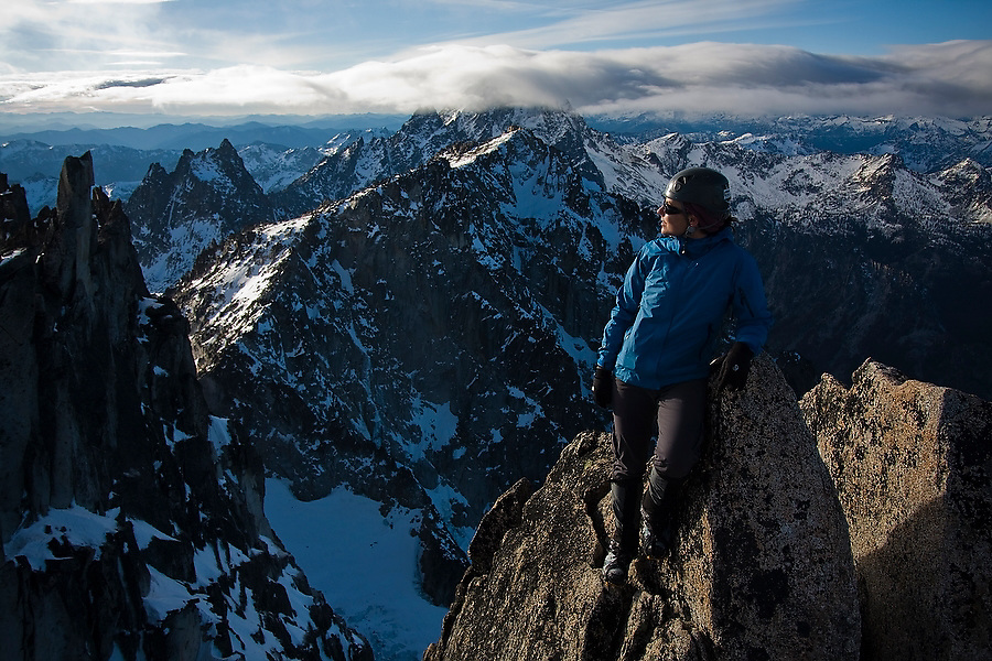 Climber Grace Marx stands on the summit block of Dragontail Peak, Alpine Lakes Wilderness, Washington. Mount Stuart is barely visible in the background.
