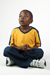 Young black boy sitting with crossed legs,