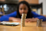 A young lady sits at her kitchen table counting her money to pay the household bills.
