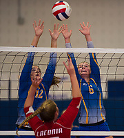 Abby Warren and Lexi Boisvert of Gilford go up for a block against Laconia's Hannah Dow during NHIAA Division II Volleyball on Saturday evening.  (Karen Bobotas/for the Laconia Daily Sun)