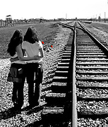 """Remember Auschwitz!  Two Norwegian girls travel for peace. Here they are at the end of the railroad track in the death camp Auschwitz II - Birkenau.  In the background the gate where more than one million judes entered to face the death in the gass chambers to full-fill the nazi's """"final solution"""" to the Judish problem."""