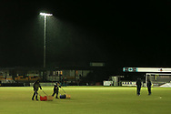 Harrogate Ground staff work to get the game on as the officials discuss the rain during the EFL Sky Bet League 2 match between Harrogate Town and Exeter City at the EnviroVent Stadium, Harrogate, United Kingdom on 19 January 2021.