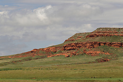 Red dirt and green grass make up a stunning view of a butte in Wyoming state.
