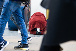A man covered in a blanket against the morning chill begs on Oxford Street whilst shoppers walk by in London as Eastern European beggars and street performers take advantage of the UK's relative wealth, squeezing opportunities for the UK's own homeless. London, December 13 2018.
