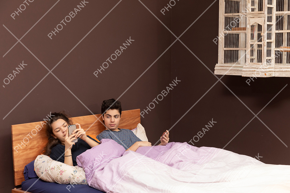 A young girl and a young boy together in the double bed. Even if they are together everyone is alone with his phone.