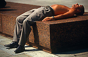 A man has chosen a free surface to spread himself out on during a lunchtime break in the City of London. Having removed his shirt and tie, he sunbathes topless with only his trousers and shoes, the clue as to his day-job in a London office. There is a heat wave in the capital and others are soaking up rays during a working week. Bronzed and asleep, the young man is carefree enough not to worry about his eccentric behaviour in a public place.