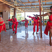 CAPTION: Members of Troupe Dahomey practice a dance routine. Through research trips, meetings and events, SPA and Troupe Dahomey are collecting songs and dances through audio and video recordings. Students work alongside them in the documentation process, capturing the talents of performers in the countryside for future generations. ORGANIZATION: Troupe Dahomey / Sant Pont Ayiti (SPA). LOCATION: La Fleur du Chaine, Rue Capois, Port-au-Prince, Haiti. INDIVIDUAL(S) PHOTOGRAPHED: From left to right: Phanor Joanne, David Dunosier, Sanon Reginald, Noël Annot Louis and Bertine Role.