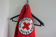 A worker's tabard hangs on a hook at the German Red Cross (Deutches Rotes Kreuz - DRK) administrative HQ at 58 Carstennstrasse, Berlin. The International Red Cross and Red Crescent Movement, with its 187 National Societies, is the world's largest humanitarian network. The German Red Cross is part of this universal community, which started 150 years ago to deliver comprehensive aid to people affected by conflict, disaster, sanitary emergencies, or social hardship, guided solely by their needs. Around four million volunteers and members support the Red Cross in Germany alone. From the chapter entitled 'A life to save' and from the book 'Risk Wise: Nine Everyday Adventures' by Polly Morland (Allianz, The School of Life, Profile Books, 2015).