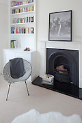 Modern lounge with white rug, chair, fireplace and bookshelf with print on the mantelpiece.