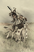 Sepia Toned Traditional Shoshone dancer photographed in Wyoming in full costume. Golden eagle feathers embellish the dance gear, bustle and headdress against stone cliffs and rolling hills.