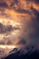 Alpenglo lit clouds swirl above Mount Jupiter at sunset, in Olympic National Forest, Olympic Mountains, as seen from the Kitsap Peninsula across Hood Canal in Puget Sound, Washington state, USA.
