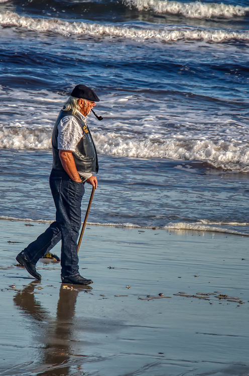 An older gentleman walking the beach, just beyond the reach of the surf, with a walking stick and a pipe.