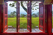 Cidadel red swinging doors open to the outside showing grass and clouds with a tree.