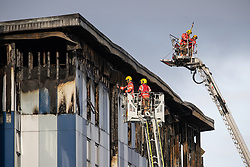 """© Licensed to London News Pictures. 16/11/2019. Bolton, UK. Firefighters examine cladding at the scene where a fire broke out overnight (15th/16th November 2019) at a block of flats known as """" The Cube """" , in Bolton Town Centre . At least two people are known to have been treated by paramedics at the scene of the six-story block , which is occupied by students of the University of Bolton . Photo credit: Joel Goodman/LNP"""