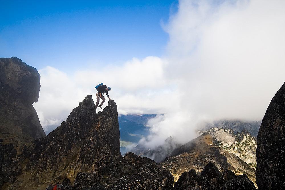 Climber Obadiah Reid scrambles up the West Ridge of Mount Stuart, Alpine Lakes Wilderness, Washington.