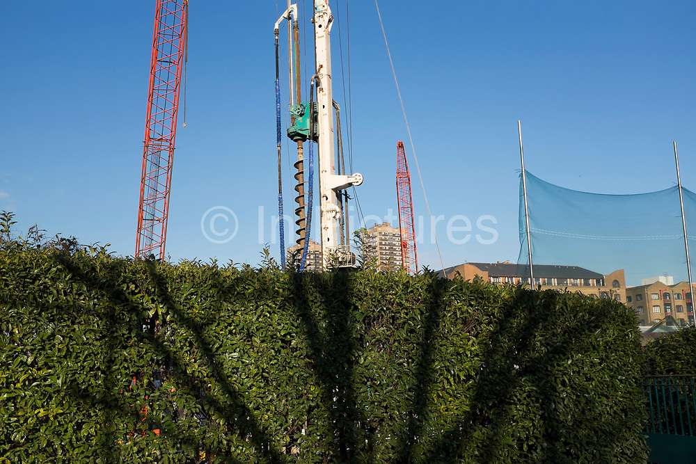 Scene of the shadow of a tree on a hedge in front of machinery on a building site. natural and man made elements. London, UK.