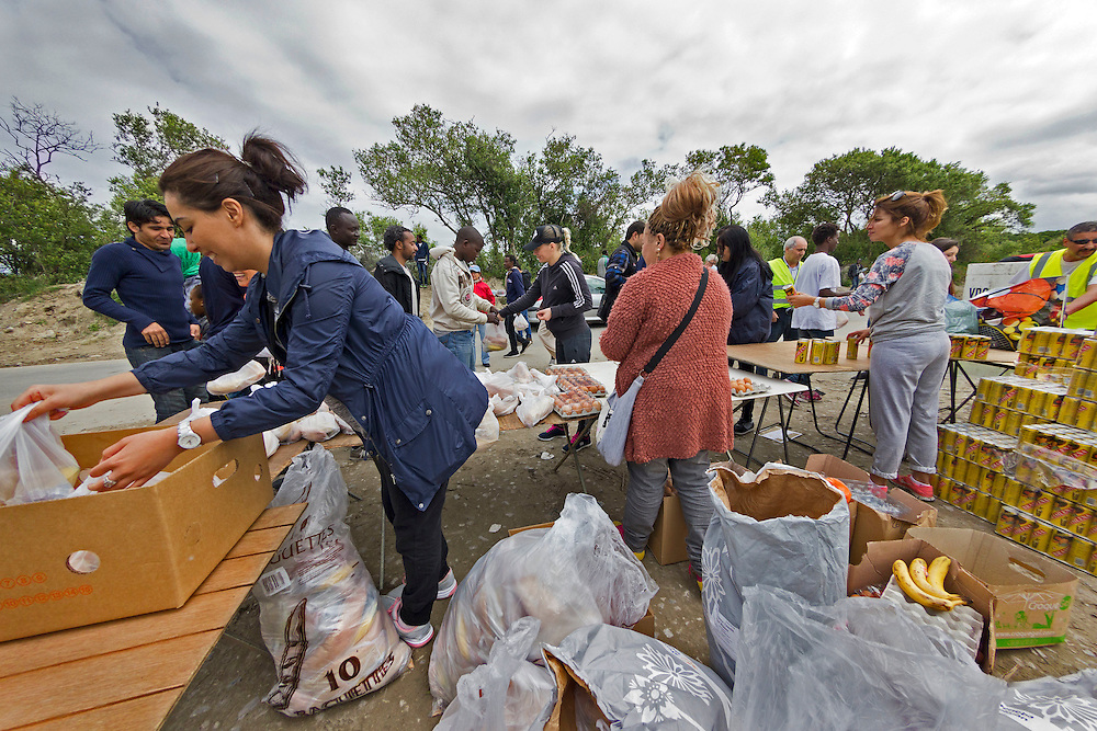 Food distribution by aid workers. The Jungle, refugee camp, France