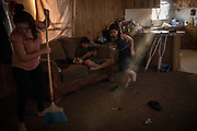 Carolina, daughter of Orfa, a Honduran migrant seeking asylum, cleans and stands in as caretaker for her younger siblings Bayron and Rachel, inside the family's rented trailer in Texico, New Mexico, U.S., February 4, 2019.