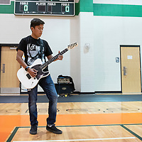 Colin Tracy, 18, a senior at Wingate High School plays the national anthem on the electric guitar Thursday night before the volleyball match between Wingate and Grants in Fort Wingate.