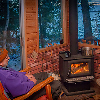 Allan Pietrasanta sits by a wood stove in a cabin on Lake of the Woods, Ontario, Canada.