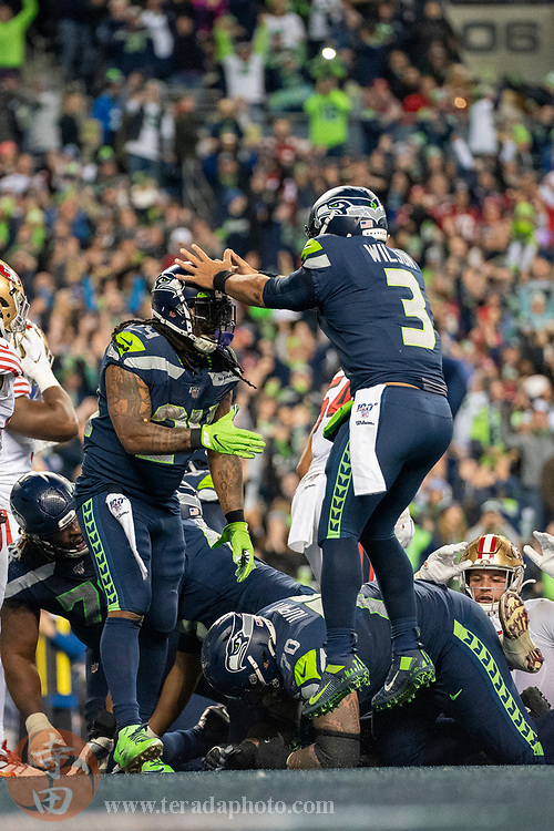 December 29, 2019; Seattle, Washington, USA; Seattle Seahawks running back Marshawn Lynch (24) is congratulated by quarterback Russell Wilson (3) for scoring a touchdown during the fourth quarter against the San Francisco 49ers at CenturyLink Field.