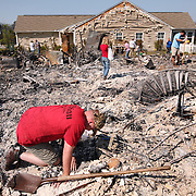 Myrtle Beach, SC - APRIL 24: Derek Boos searches through the wreckage of his mother and father-in-law  after wildfires ravaged homes on April 24, 2009 in Myrtle Beach, SC. South Carolina Gov. Mark Sanford declared a state of emergency Thursday for a coastal county where a wildfire has consumed thousands of acres and destroyed dozens of homes. (Photo by Logan Mock-Bunting/Getty Images)