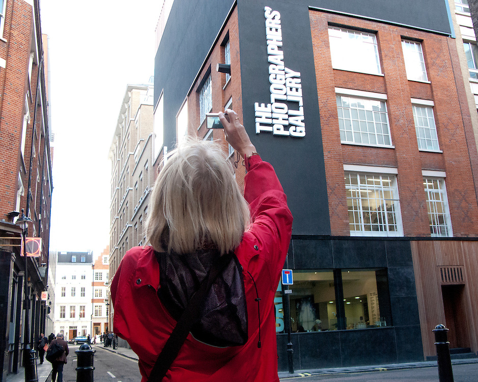 A female tourist taking a picture outside the photographers galley in London