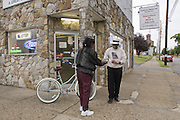 Author Norris Shelton, owner of Mr. Silk's Liquors at 2100 West Muhammad Ali Boulevard, gives a dollar to a woman panhandling outside his store Tuesday Sept. 26, 2011 in Louisville, Ky. (Photo by Brian Bohannon)