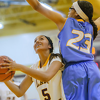 Tohatchi Cougar Kalian Mitchell (5) shoots around a block attempt from Dulce Hawk Caitlin Duncan (23) Friday at Tohatchi High School.