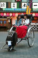 Asakusa Rickshaw with Japanese women tourists having a photo op with the rickshaw puller.