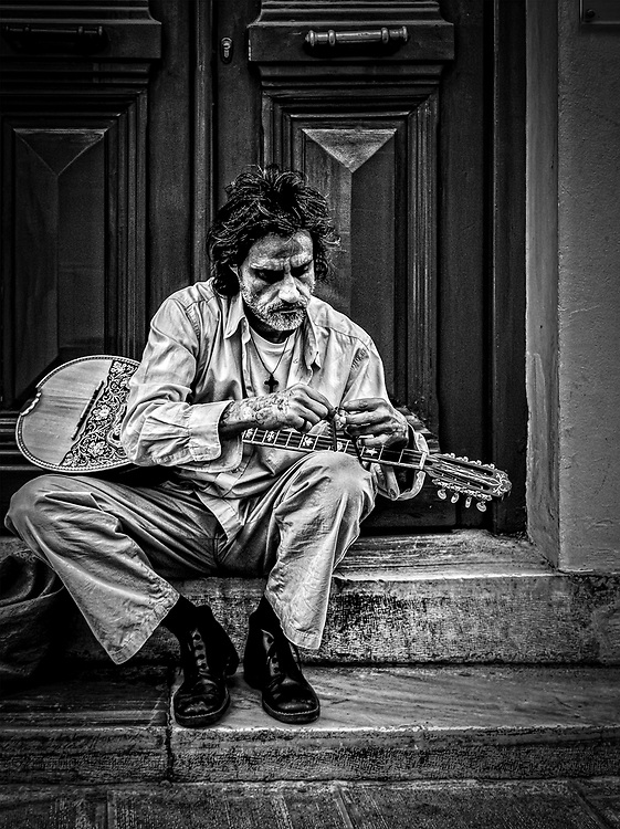Street musician. Bouzouki player in Athens sitting on the stairs. Black and white