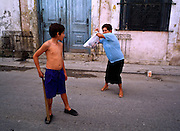 HAVANA, CUBA: A woman shows her nephew how to play stickball (baseball) on a street in the central section of Havana, Cuba.    Photo by Jack Kurtz  WOMEN  SPORTS  CHILDREN  CULTURE  FAMILY