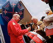 Pilot of the Red Arrows, Britain's RAF aerobatic team signs publicity brochures for the public during airshow.