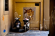 Parked motorbikes with classical graffiti, Florence.