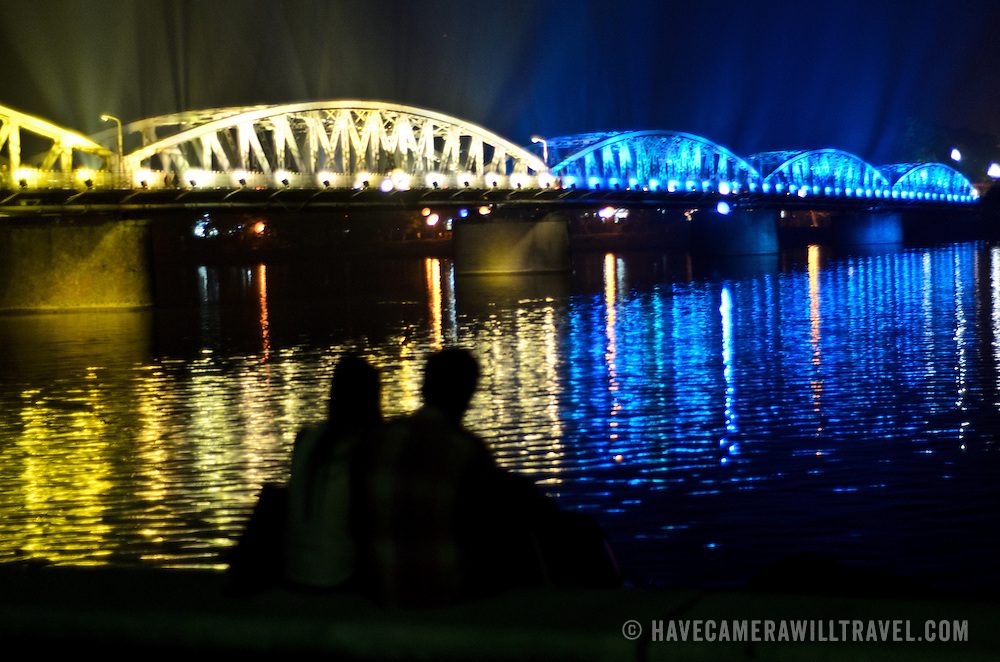 A couple sits on the waterfront of the Trang Tien Bridge across the Perfume River in Hue, Vietnam, at night, silhoutted against the brigh illumination of the bridge.