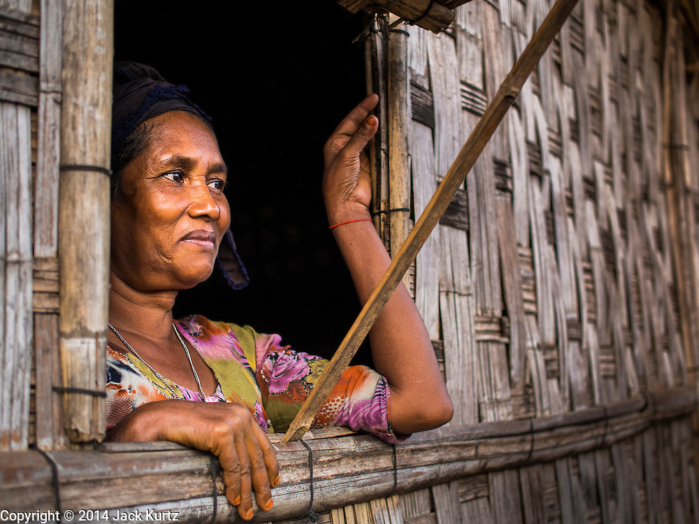 05 NOVEMBER 2014 - SITTWE, RAKHINE, MYANMAR: A Rohingya Muslim woman looks out the window of her hut in a Rohingya Muslim IDP camp near Sittwe. After sectarian violence devastated Rohingya communities and left hundreds of Rohingya dead in 2012, the government of Myanmar forced more than 140,000 Rohingya Muslims who used to live in and around Sittwe, Myanmar, into squalid Internal Displaced Persons camps. The government says the Rohingya are not Burmese citizens, that they are illegal immigrants from Bangladesh. The Bangladesh government says the Rohingya are Burmese and the Rohingya insist that they have lived in Burma for generations. The camps are about 20 minutes from Sittwe but the Rohingya who live in the camps are not allowed to leave without government permission. They are not allowed to work outside the camps, they are not allowed to go to Sittwe to use the hospital, go to school or do business. The camps have no electricity. Water is delivered through community wells. There are small schools funded by NOGs in the camps and a few private clinics but medical care is costly and not reliable.   PHOTO BY JACK KURTZ