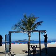 Locals work out at a fitness station at the edge of Ipanema beach, Rio de Janeiro,  Brazil. 4th July 2010. Photo Tim Clayton....